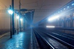 Stazione ferroviaria alla notte Binario del treno in nebbia Ferrovia Fotografia Stock Libera da Diritti