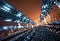 Stazione ferroviaria alla notte Binario del treno in nebbia Ferrovia Fotografie Stock