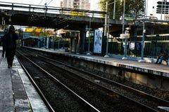 Stazione ferroviaria con qualche gente che aspetta all'alba Immagine Stock Libera da Diritti