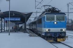 Stazione Marianske Lazne con i treni nel giorno di inverno scuro della neve fotografia stock