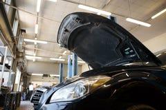 Stazione nera di riparazione dell'automobile con il morbido fuoco nei precedenti e sopra luce Fotografia Stock