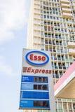 Stazione precisa del combustibile della benzina di Esso con la grande costruzione di appartamento Immagini Stock Libere da Diritti
