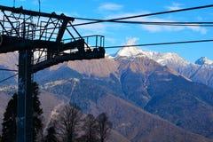 Stazione sciistica, contro il contesto delle montagne, le cime nella neve fotografie stock libere da diritti