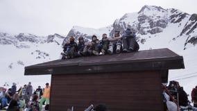Stazione sciistica Gli Snowboarders che si siedono sul tetto della casa dentro campeggiano Mano di Wave in camera stock footage