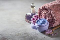 Stazione termale Crema naturale, sale marino, fiori e un asciugamano Copi lo spazio del fondo immagine stock