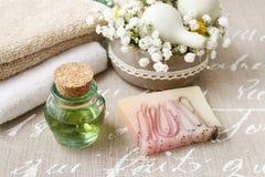 Stazione termale messa: bottiglia di olio essenziale, asciugamani molli, pezzo di sapone Immagine Stock