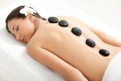 Stazione termale Tretment. Bella donna che ottiene massaggio delle pietre Immagini Stock Libere da Diritti