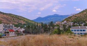 Stazione turistica residenziale con le grandi case ed i piccoli cottage contro il contesto delle catene montuose senza fine Immagine Stock