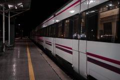 Stazione vuota della strada di ferrovia alla notte Il treno sta andando sulle piste immagini stock