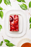 Stück des Kuchens mit Erdbeeren und Gelee, Tasse Tee und frische grüne Blätter Lizenzfreies Stockfoto