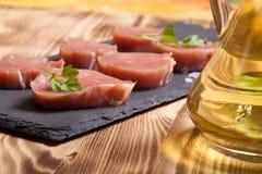 Stücke rohes Fleisch auf einer Platte von Schieferkrautgewürzen und von olivgrünem oi Stockbilder