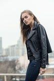 Städtisches Mädchen, das in einer Lederjacke auf einer Dachspitze aufwirft Stockbilder