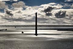 25ste April Bridge in Lissabon onder bewolkte hemel Stock Foto