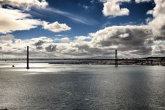 25ste April Bridge in Lissabon onder bewolkte hemel Stock Foto's
