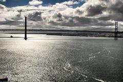 25ste April Bridge in Lissabon onder bewolkte hemel Stock Fotografie