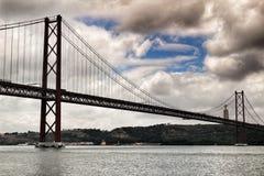 25ste April Bridge in Lissabon op een bewolkte dag Stock Afbeeldingen