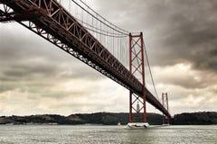 25ste April Bridge in Lissabon op een bewolkte dag Stock Afbeelding