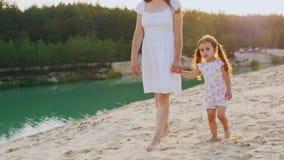 Steadicam射击了:妈妈由沿美丽的海滩的手带领一个女儿在湖和森林背景  股票视频