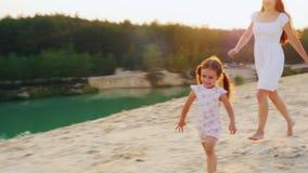 Steadicam射击了:愉快的童年,使用与她的海滩的女儿的母亲 女孩笑和奔跑远离他的 股票录像