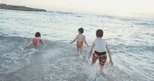 Steadicam使用在海滩的射击了三个小孩在日落期间 股票录像