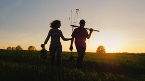 Steadicam射击了:农夫一对年轻夫妇沿领域走 他们运载种植的树设备 在 影视素材