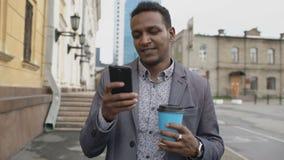 Steadicam射击了年轻愉快的商人使用智能手机和走与咖啡户外