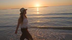 Steadicam走在海滩的射击了一名年轻美丽的妇女在日落期间 股票视频