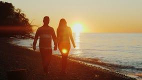 Steadicam сняло: молодые мульти-этнические пары держа руки, идя вдоль seashore на заходе солнца Азиатские человек и кавказец стоковое фото