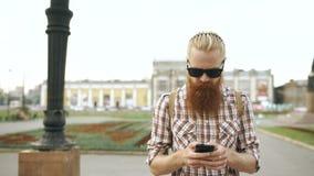 Steadicam сняло бородатого туристского человека с улицей рюкзака идя и использовать для карты взгляда smartphone outdoors сток-видео