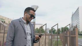 Steadicam сняло молодого бизнесмена смешанной гонки слушая к музыке на его smartphone outdoors
