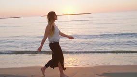 Steadicam сняло молодой красивой женщины идя на пляж во время захода солнца акции видеоматериалы