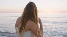Steadicam сняло молодой красивой женщины идя на пляж во время захода солнца сток-видео