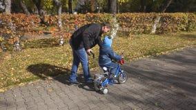 Steadicam сняло сына отца уча как ехать его велосипед на тропе парка с шлемом безопасности акции видеоматериалы