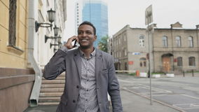 Steadicam сняло танцев бизнесмена смешанной гонки радостных и говоря телефона о его новой карьере акции видеоматериалы