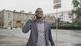 Steadicam сняло танцев бизнесмена смешанной гонки радостных и говоря телефона о его новой карьере