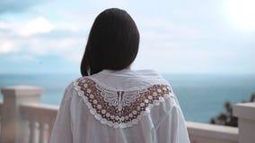 Steadicam устанавливает женщину съемки причаливая к античным белым перилам восхищая изумительное море акции видеоматериалы