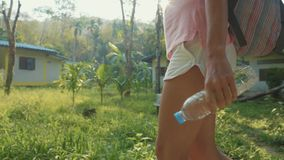 Young woman walking on countryside path through asian village, slow motion. Steadicam crop shot of young backpacker woman walking alone on a countryside path stock video footage