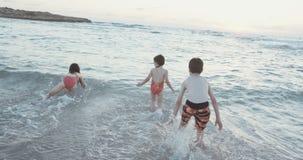 Steadicam disparou de três crianças que jogam na praia durante o por do sol vídeos de arquivo