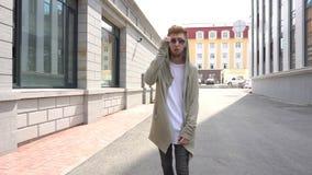 Steadicam disparou de um homem considerável novo na roupa à moda que anda ao longo da rua vídeos de arquivo