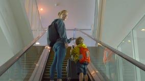 Steadicam disparou de uma jovem mulher e de seu filho pequeno que vão acima usar uma escada rolante em um aeroporto filme