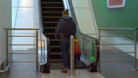 Steadicam disparou de uma jovem mulher e de seu filho pequeno que vão acima usar uma escada rolante em um aeroporto video estoque