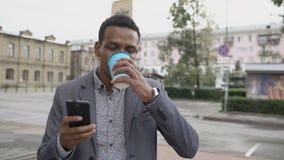 Steadicam disparou do homem de negócios feliz novo que usa o smartphone e andando com xícara de café fora