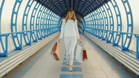 Steadicam disparou: Jovem mulher à moda com sacos de compras que fala na transição de vidro moderna ou em um túnel filme