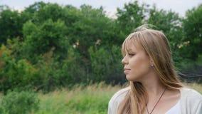 Steadicam disparou: Retrato de uma mulher gravida nova que anda no prado com um ramalhete dos wildflowers video estoque
