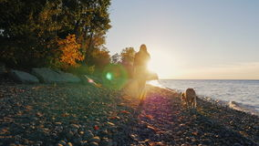 Steadicam disparou: Silhueta de uma jovem mulher Anda com um cão perto de um lago ou do mar no por do sol Céu muito bonito filme
