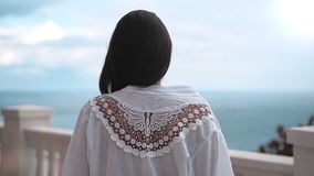 Steadicam establece a la mujer del tiro que se acerca a la verja blanca antigua que admira el mar asombroso almacen de metraje de vídeo