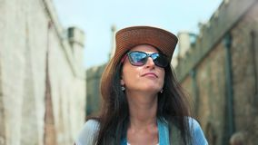Portrait active backpacker woman in sunglasses and hat walking tourist place enjoying architecture. Steadicam establish shot portrait of active backpacker woman stock footage