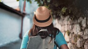 Steadicam establish shot rear view backpacker tourist woman enjoying walking narrow street. With antique building. Medium close-up active female hiker in hat stock video footage