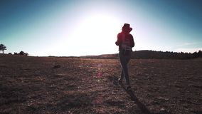 Silhouette of slender sports female in hat with backpack walking on field at sunset. Steadicam establish shot rear view silhouette of slender sports female in stock video footage