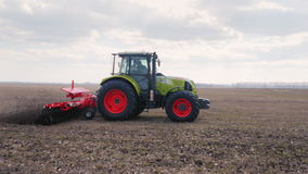 Steadicam fly around shot: The tractor plows the land on the field. Agribusiness is modern stock footage